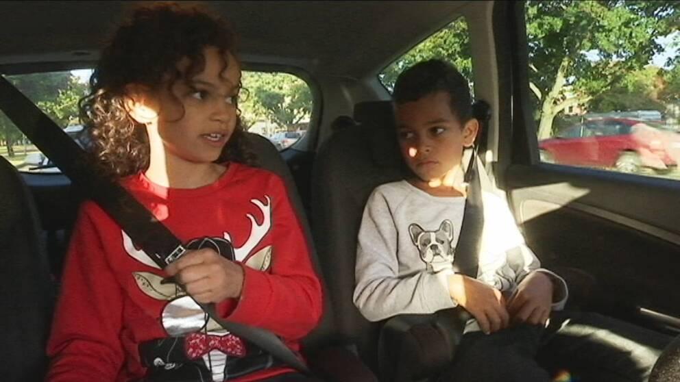 Två syskon sitter i baksätet på en bil. En åttaårig flicka och en sexårig pojke. De har säkerhetsbälten på sig.