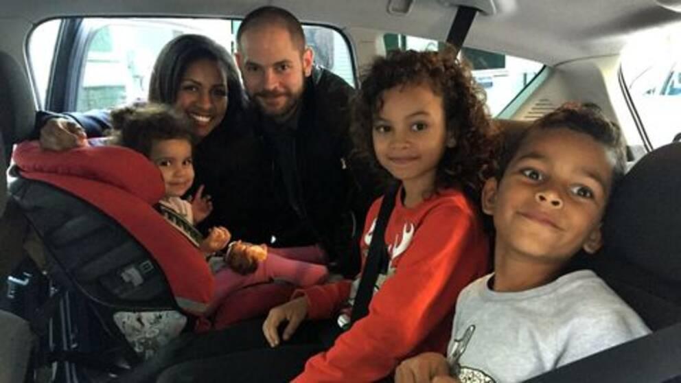 Två föräldrar kikar in i baksätet på en bil. Där sitter deras tre barn. Alla tittar mot kameran.