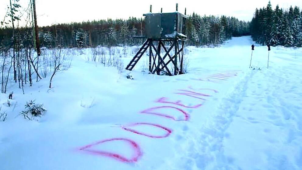 """Jakttorn i snö med texten """"Dödens ring"""" skrivet med röd text i snön nedanför"""