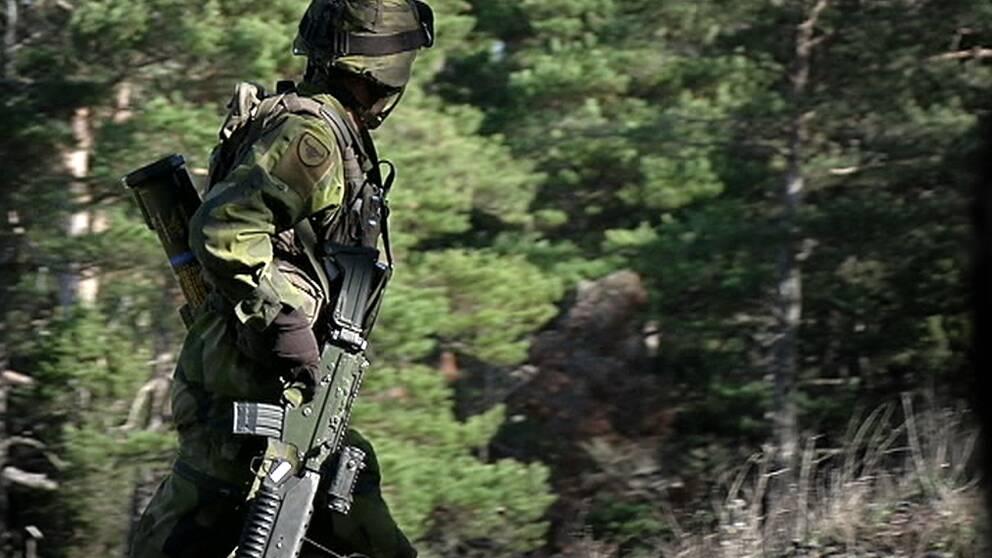 Soldat i uniform och vapen går i skog.