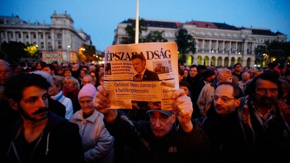 En demonstrant håller upp det sista tryckta exemplaret av den nu nedlagda oppositionella tidningen Népszabadság.