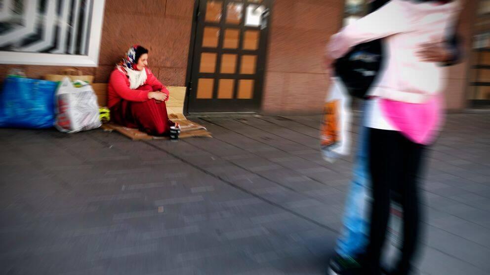 Kvinna sitter och tigger vid husvägg