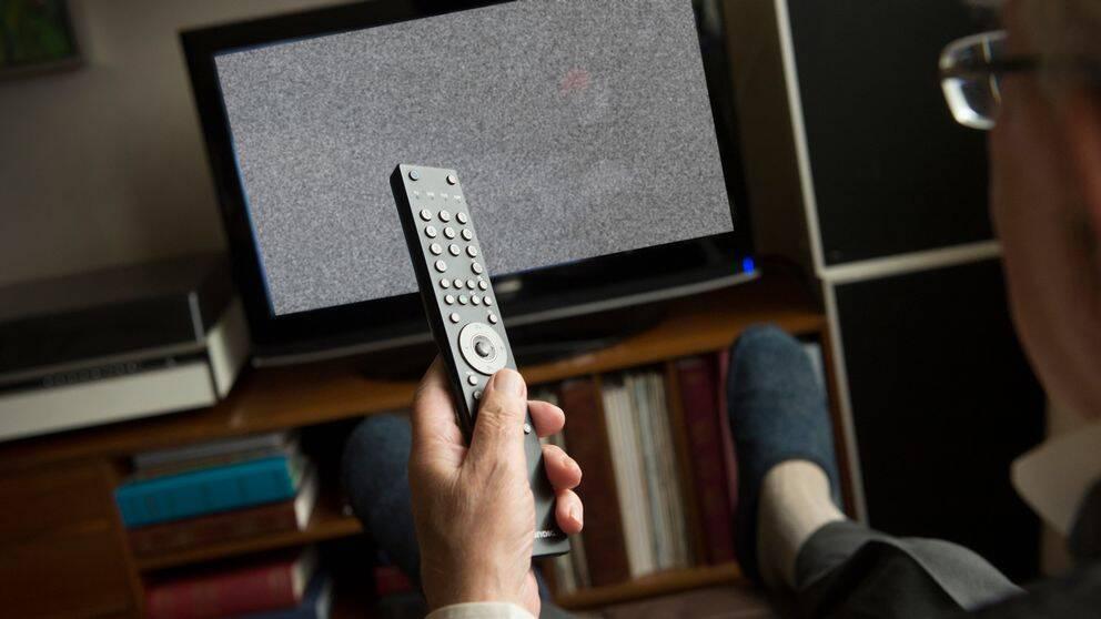 En bild på en man som sitter framför en TV.