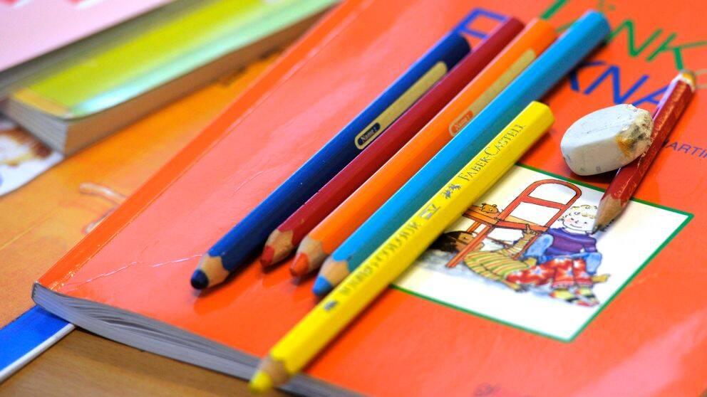 Skolbok och pennor.