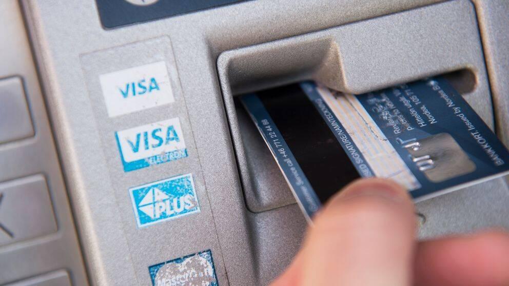 En bild på någon som sätter in ett bankkort i en bankomat.