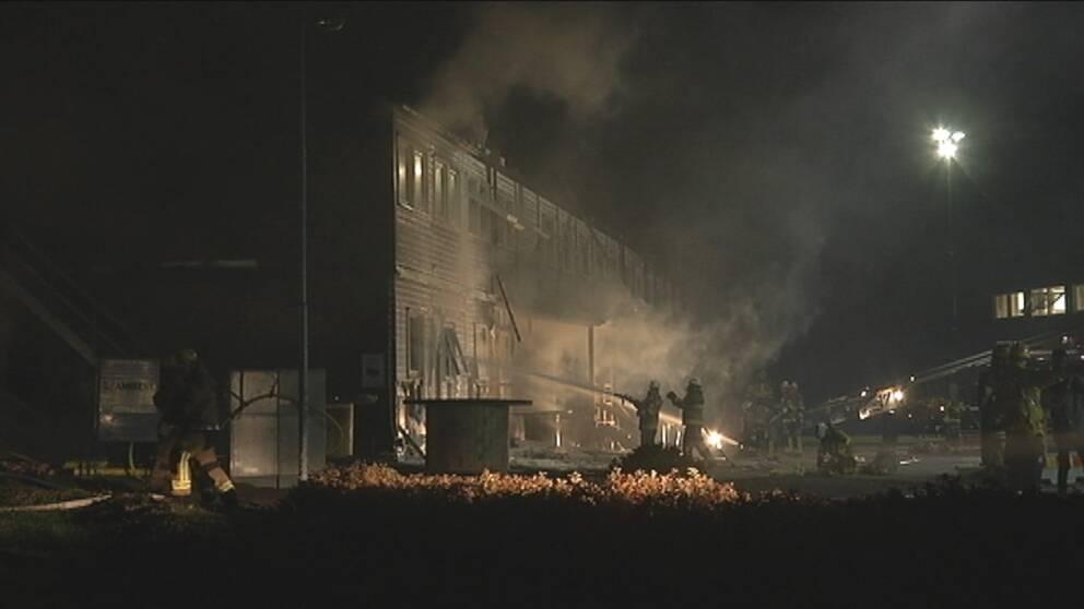 Brandmän kämpar med att släcka elden på flyktingboendet i Farsta.