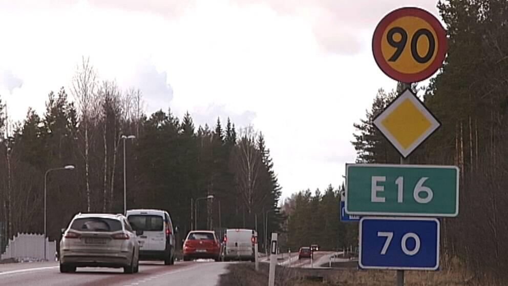 Vägskylt E16 med väg och bilar i bakgrunden
