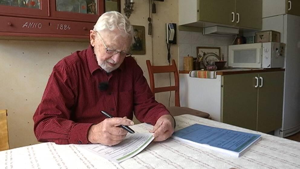Stig Sköld sitter vid sitt bord och fyller i ett formulär.
