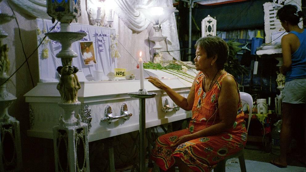 Nelly Alberto vakar över sitt barnbarn Noel Albertos kista ute på gatan i Tondo, Manilla. En vaka hålls vanligtvis i några dagar men Noel Albertos kropp har legat så här i över två veckor nu.