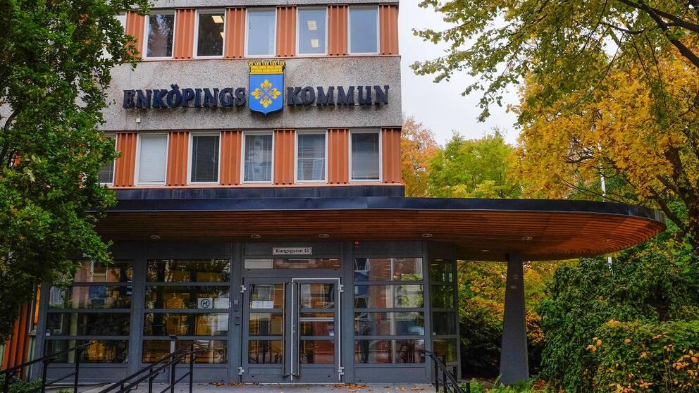 Ett foto på Enköpings kommunhus, det är höst och löven på träden har börjat bli gula.