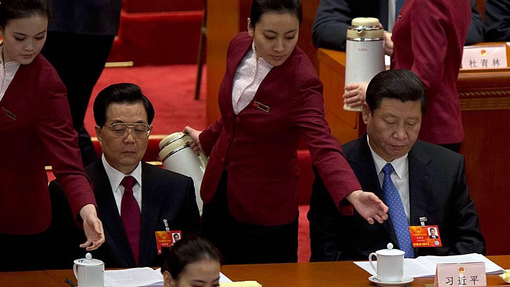 Kinas avgående president Hu Jintao och hans förväntade efterträdare Xi Jinping får påfyllning av te av två värdinnor vid folkkongressens öppnande.