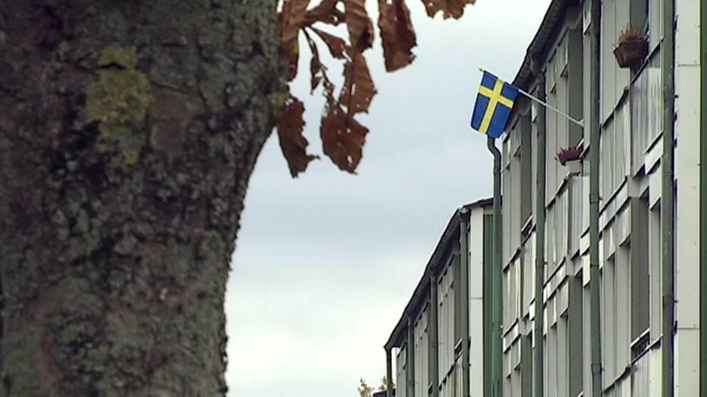 Lägenhetshus utifrån med svensk flagga vajande från en balkong.