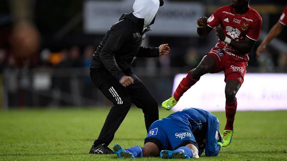 Maskerad man på en fotbollsplan. En spelare ligger på marken, en annan är på väg mot den maskerade mannen.