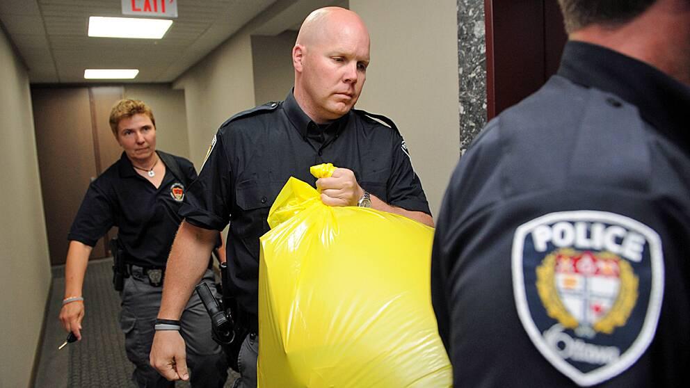 En polisman bär ut paketet, som innehöll en mänsklig fot, från Kanadas konservativa partis högkvarter i Ottawa.