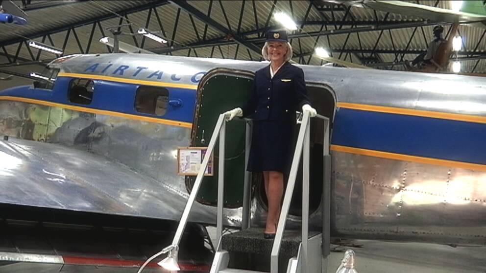 Den tidigare flygvärdinnan Reidun Boethius står på trappstegen till ett flygplan.