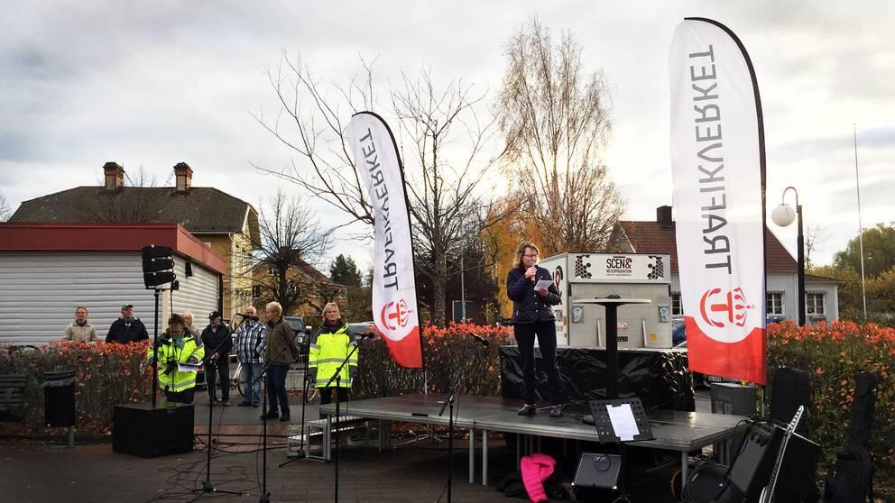 Kommunalrådet Marie Wilén (C) talar från en scen på torget i Heby. I bakgrunden står åhörare.