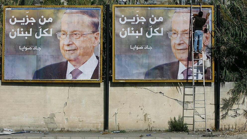 Bilder på Michel Aoun sätts upp i hamnstaden Saida.
