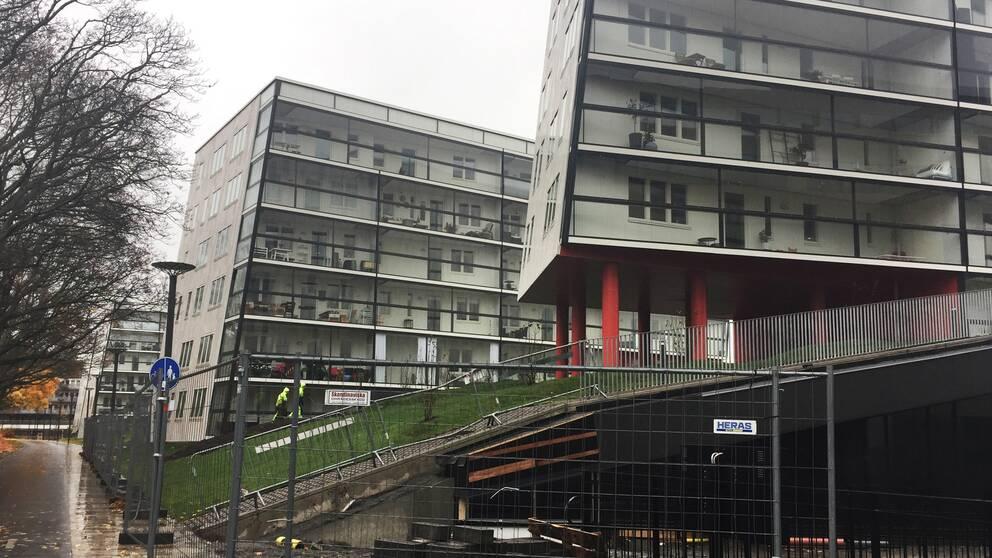 Bild på Uppsala Entré, ett stängsel skärmar av husen från en gångväg.