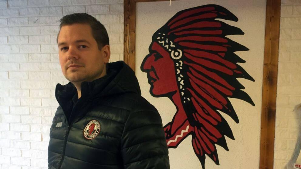 Indianernas nya lagledare Peter Johansson framför en Indianlogga.