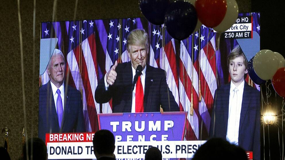 Guests watch a television broadcast of President-elect Donald Trump as he gives his acceptance speech, during an election night event organized by the U.S. Embassy in Skopje, Macedonia, Wednesday, Nov. 9, 2016. Trump defeated Hillary Clinton to be elected the 45th president of the United States. (AP Photo/Boris Grdanoski)