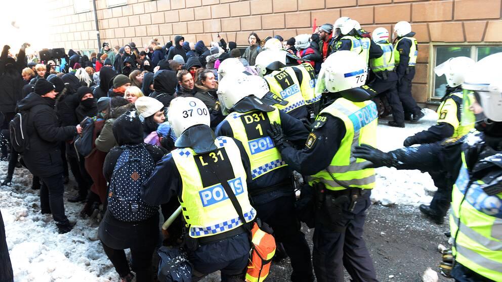 Motdemonstranter hålls på avstånd av polisen när Nordiska motståndsrörelsens demonstration går från Kungsträdgården till Mynttorget i Stockholm under lördagen.