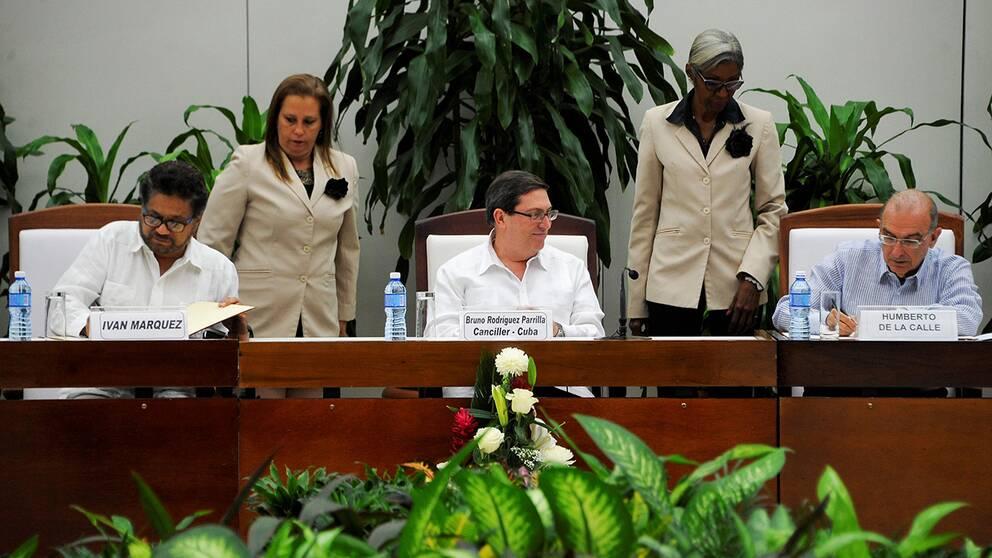 Farc-ledaren Ivan Marquez och Humberto de la Calle, ansvarig för fredsförhandlingarna för Colombias räkning, skriver på ett nytt fredsavtal.