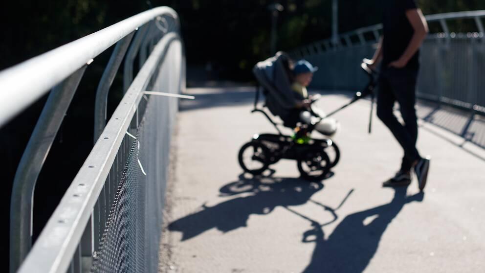 oidentifierbar man med barn i vagn på gångbro