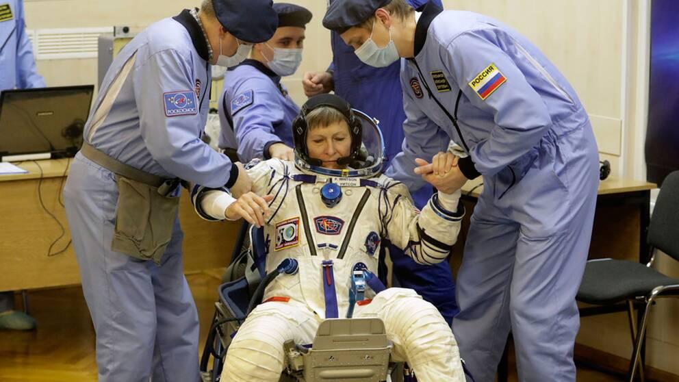 Astronauten Peggy Whitson, en av besättningsmedlemmarna på ISS, får hjälp att resa sig efter att hennes rymddräkt inspekterats före avfärden från Baikonur.