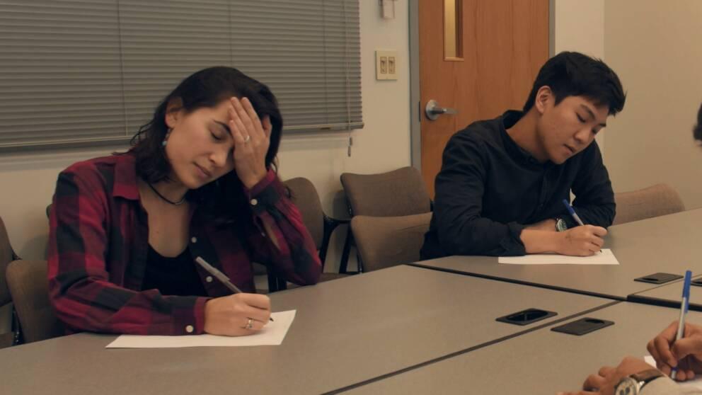 En bild på ett par studenter som skriver ner vad de minns.