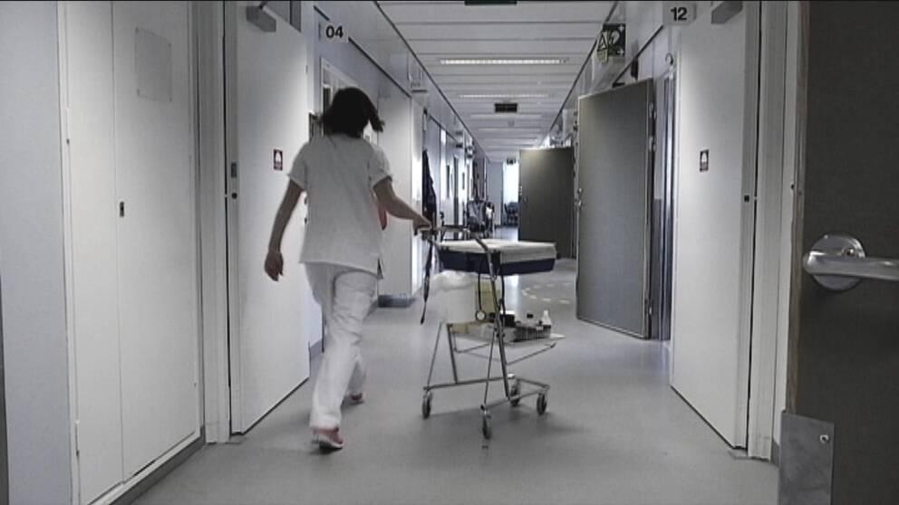 sjuksköterska går med vagn i korridor