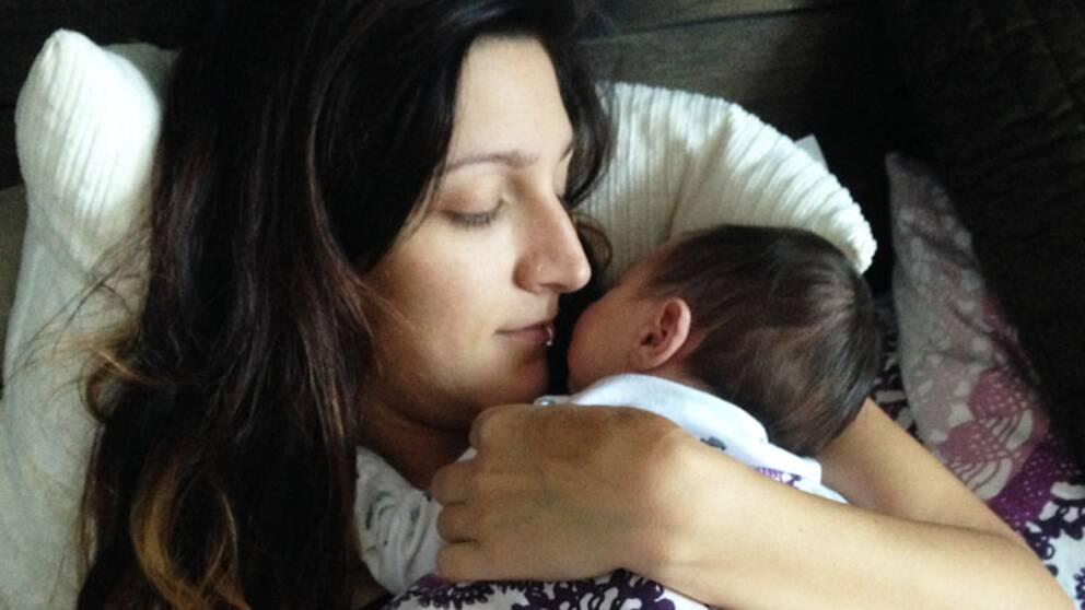 En nyfödd bebis ligger i sin mammas famn. Över dem ligger ett täcke. Mamman tittar ned på barnet. Deras ansikten är nära varandra.