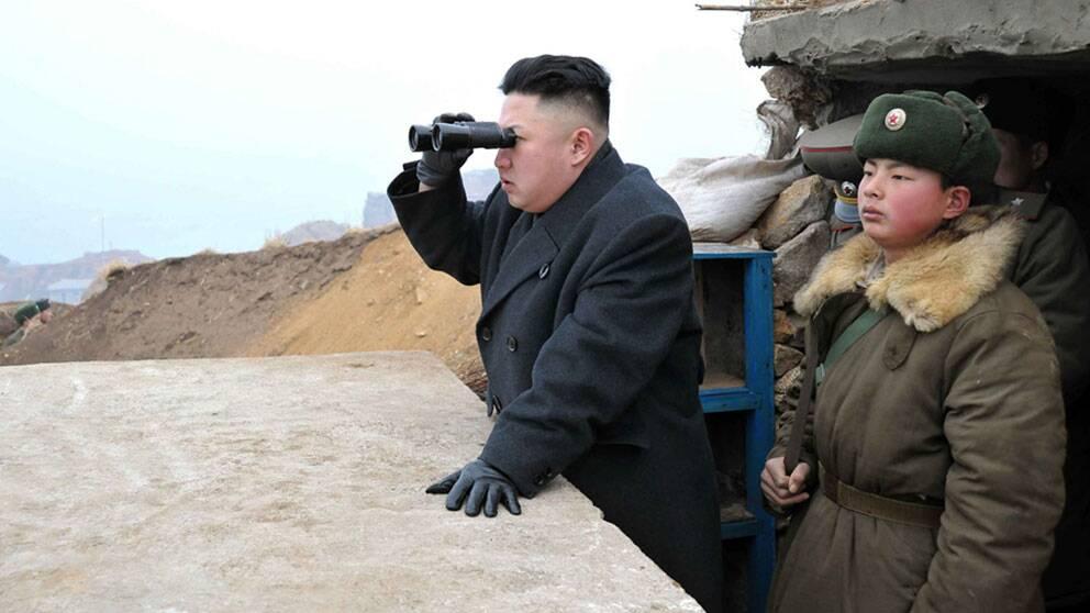Kim Jong-Un tittar mot den sydkoreanska gränsen med ett par kikare.