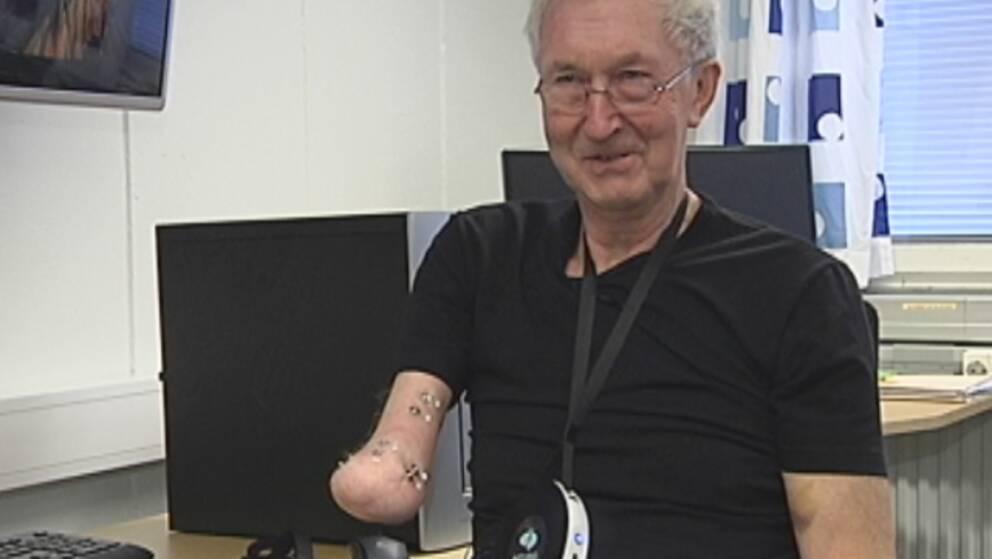 Porträtt av Ture Johansson som skrattar mot kameran. Hans högra underarm är amputerad och han har fäst små elektroder vid den.