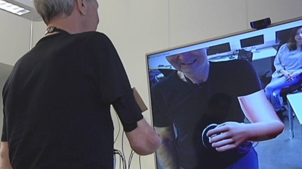 Ture Johansson står framför en skärm och skrattar åt sin animerade arm.