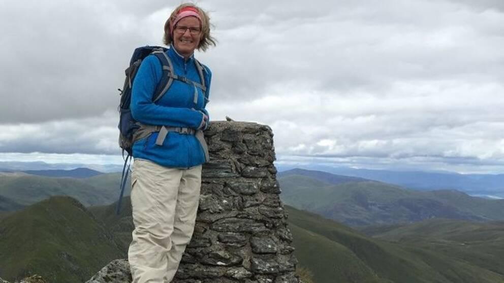 Kvinna står på ett högt berg.