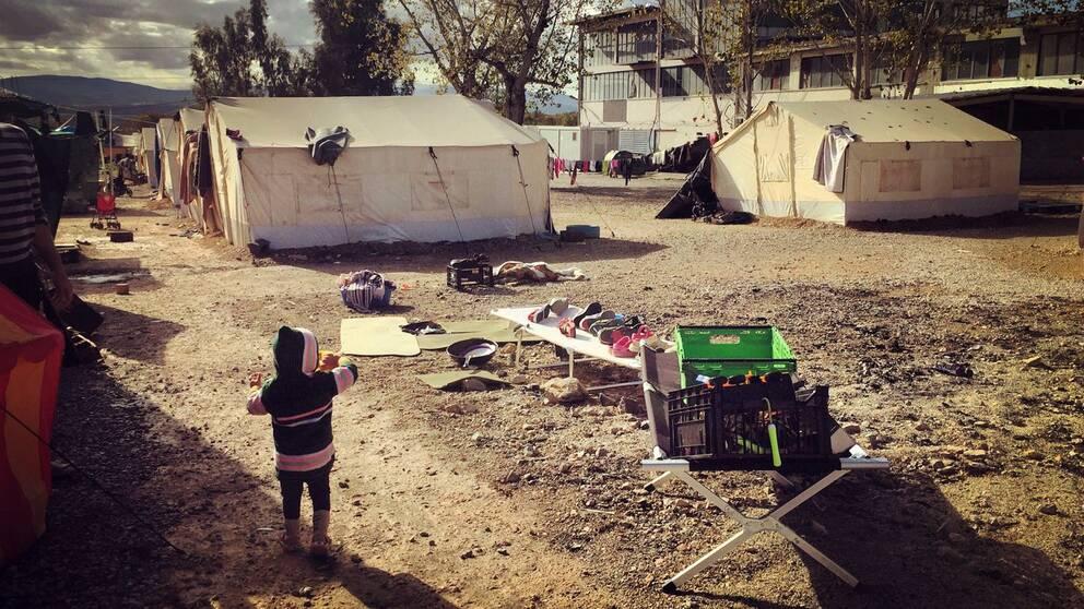 En familj städar upp efter kraftiga regn i flyktinglägret Oinofyta.