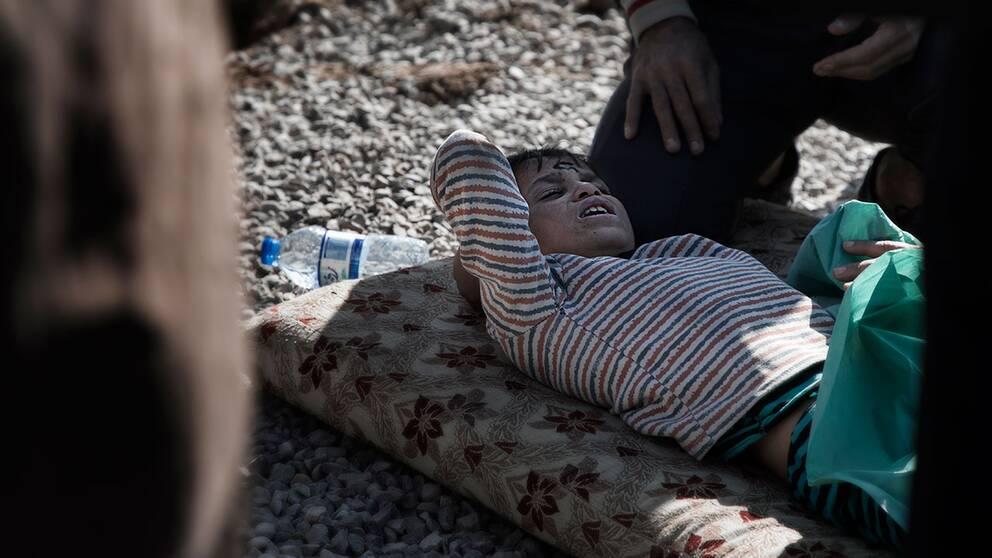 En mamma tröstar sin pojke som gråter av smärta utanför fältsjukhuset.