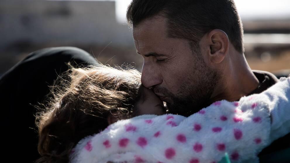 En pappa håller om sin skadade dotter i väntan på läkare.