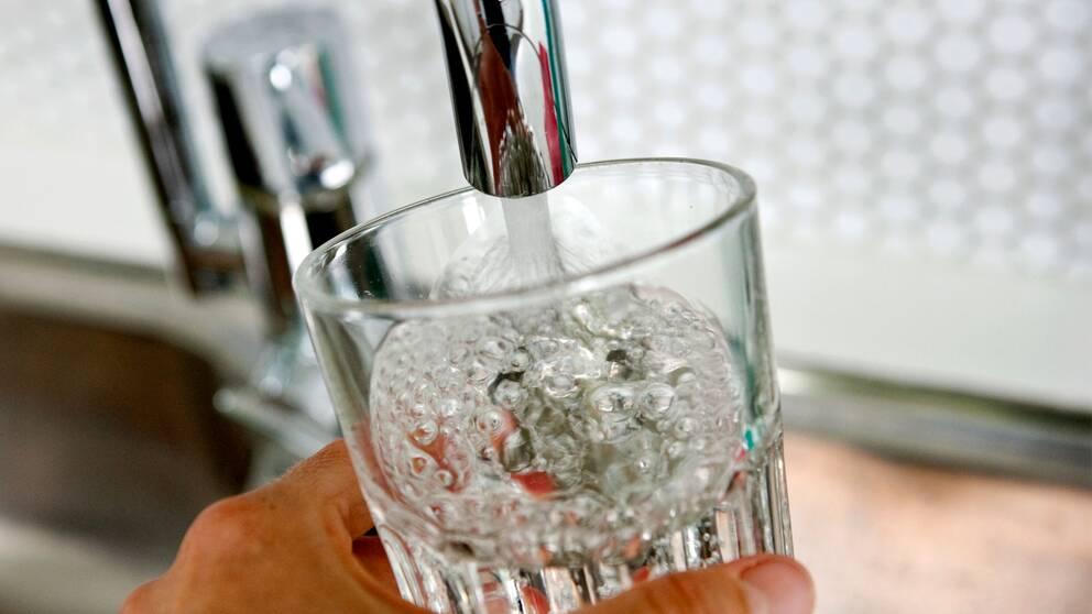 Vattenglas fylls på under en kran