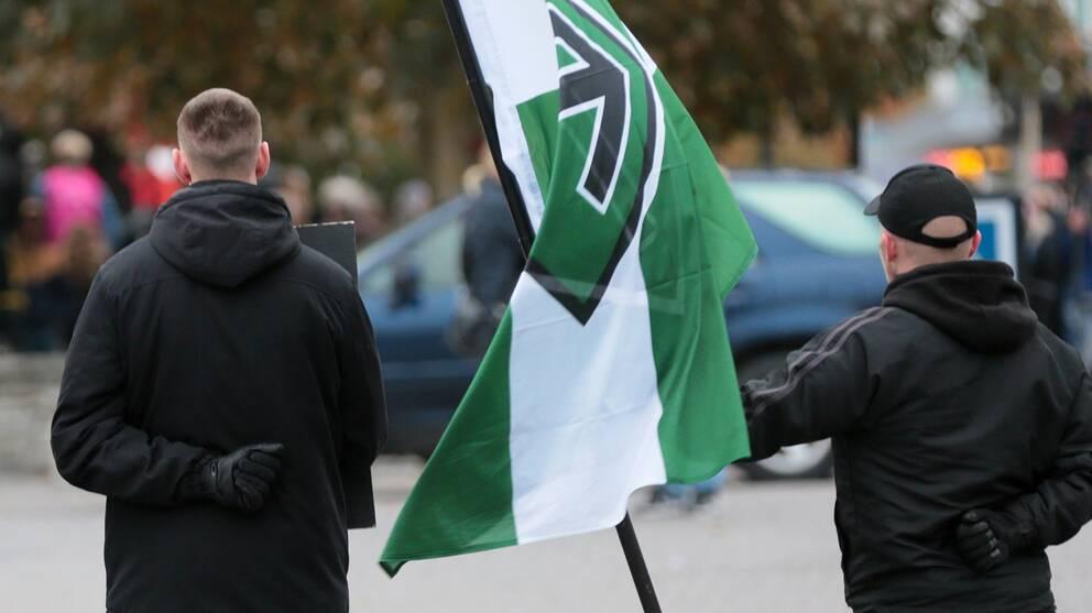 två män ses bakifrån på torg, håller flagga med rörelsens motiv