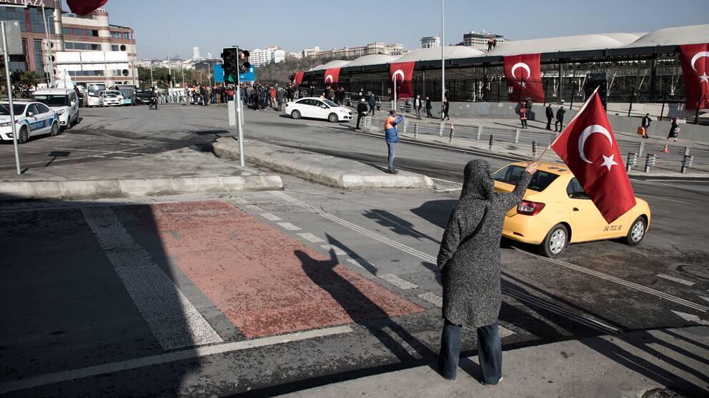 En person med en Turkisk flagga utanför stadion.