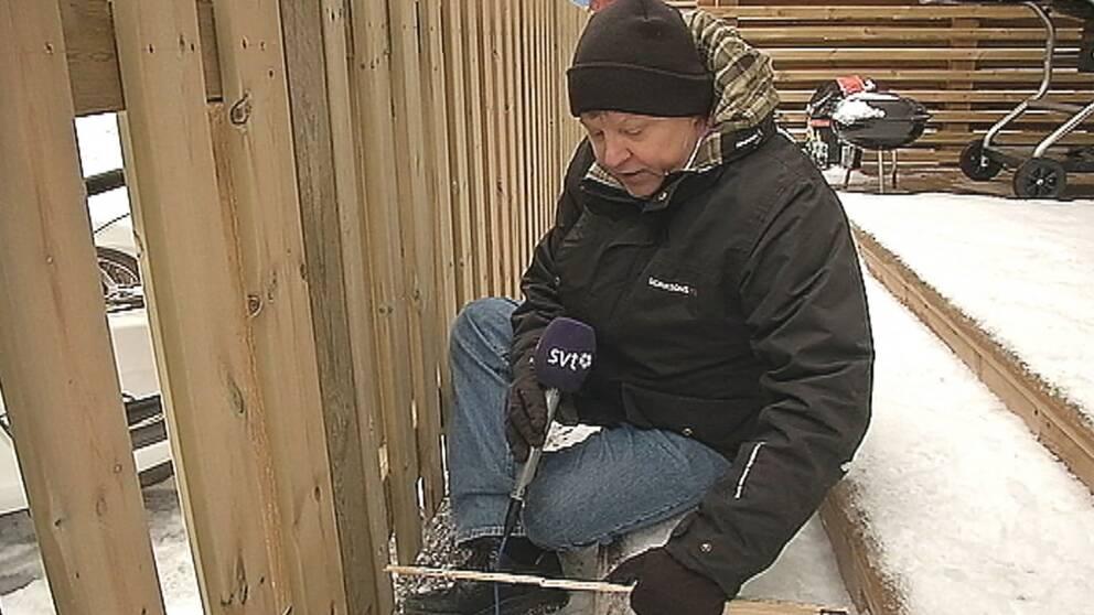 en man på trappsteg mellan snöig altan och staket