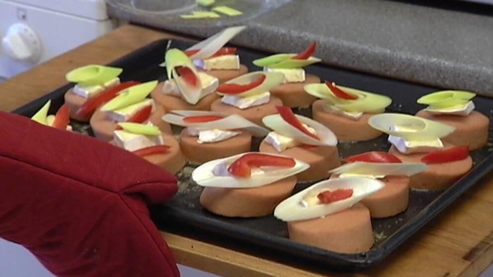 Falukorv dekorerad med brieost, paprika och purjolök.