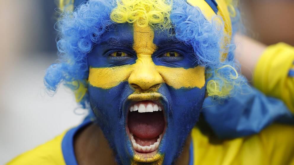 En man med svenska flaggan målad i ansiktet.