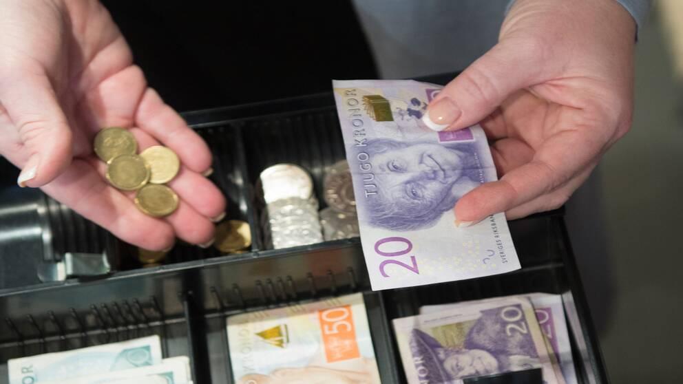 händer som tar upp pengar ur kassa-apparat.
