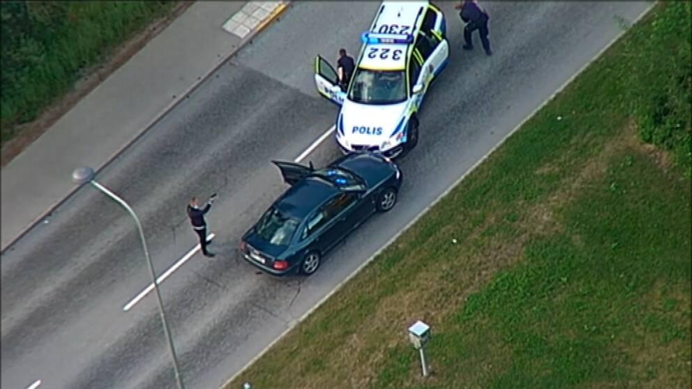 Man med polisattrapp vid två bilar, varav en är en polisbil. Två poliser på väg att ta skydd bakom polisbilen.