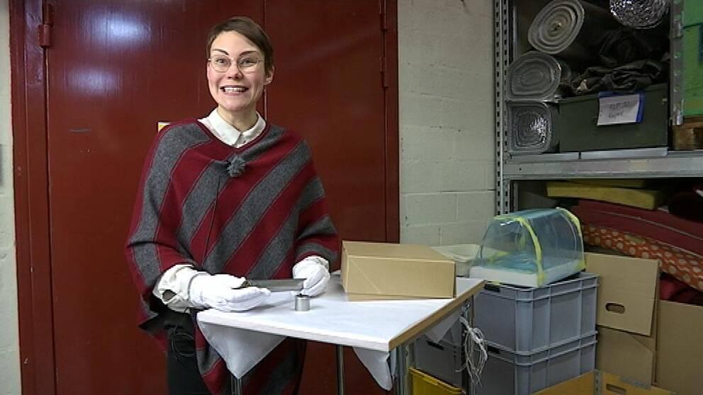 Linnea Holmberg Wensby, föremålsintendent på Flygvapenmuseum, håller i rapporthylsan som donerades till muséet under hösten.