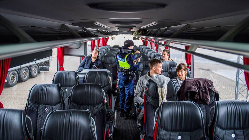 Polis utför en kontroll av id-handlingar på en buss som tar passagerare mellan Danmark och Sverige.