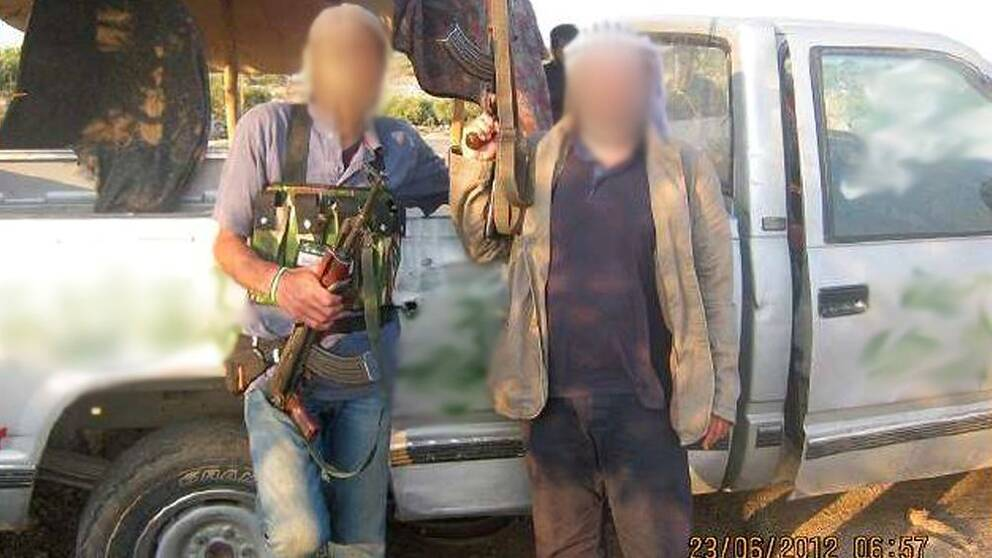 Bild på två personer som poserar framför en bil med ett varsitt vapen i handen.