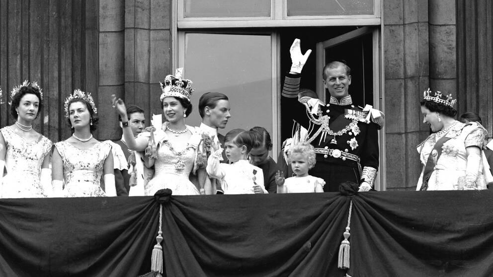 Elizabeth vinkar från balkongen efter sin kröning. På bilden syns barnen Charles och Anne, och maken Philip.